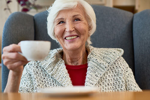 An image of a resident at University Village holding a coffee cup.